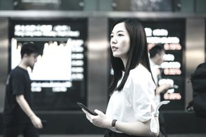 young woman with phone considers stock market numbers