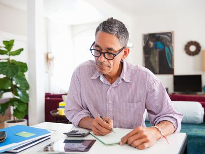 A man seated at a table taking notes