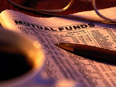 Finance section of newspaper folded to mutual funds listings placed under a pen, glasses and a cup of coffee