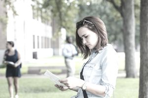 Young college student studying a campus map outside of a dorm building