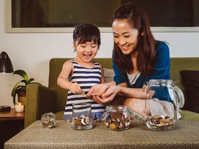 Mother and daughter putting coins in jars