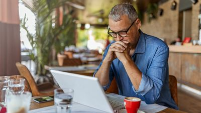 A mature man looks stressed as he reviews his financial statements on a laptop.
