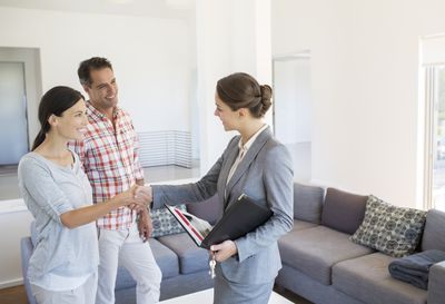 realtor and couple shaking hands in living room