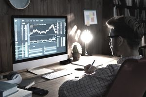 Man looking at computer screen with stock-market chart
