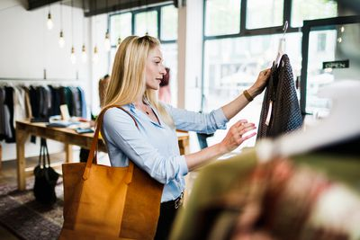 Woman Reading Label On Clothing While Out Shopping
