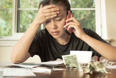 Stressed woman with no money looking at her credit card bills and monthly payments.