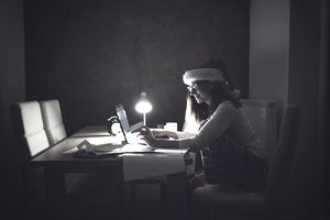 Woman wearing Santa hat working on a laptop