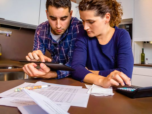 Unhappy couple at a kitchen counter with a tablet, calculator, and bills