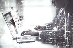 Double exposure businessman hands working on laptop with chart finance and technology