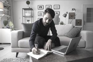 A man completes paperwork on a coffee table with a laptop nearby.