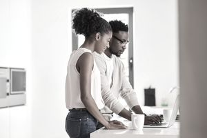 Shot of a young couple using a laptop at home