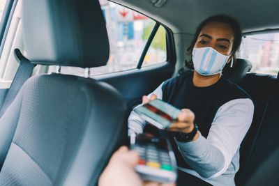 Woman makes a payment with her mobile wallet in a rideshare