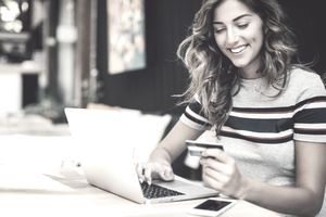 Smiling young woman holding a credit card and typing on a laptop.