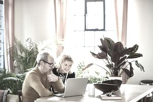 Middle-aged man and wife look at a laptop together in their home.