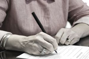 Woman signing signature on document