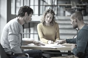 Three colleagues comparing their notes in open-concept office