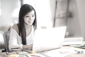 female college student budgeting with laptop