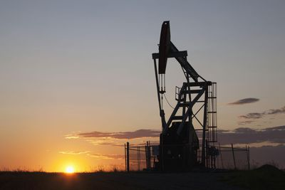 Silhouette Of Pump Jack With The Orange Glow Of The Sun Rising On The Horizon