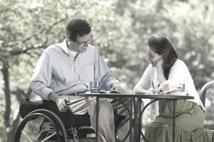 Man in wheelchair reading book with woman