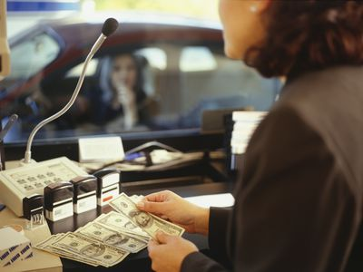 Female teller counting out bills for withdrawal for female customer in drive-through at credit union