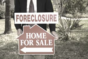 Realtor holds foreclosure for sale sign in the front yard of a home.