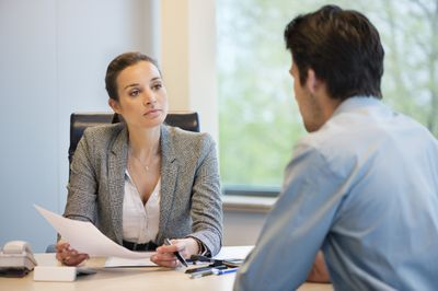 A hiring manager works her way through interview questions with a man seated at her desk