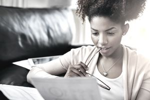 Shot of a young woman going through her paperwork at home