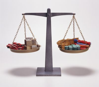 Model scales showing balance of assets, including automobiles and oil barrels