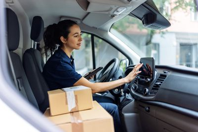 Delivery woman driving van with packages on the front seat.