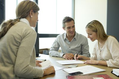 Two happy people signing contract at businesswoman's desk