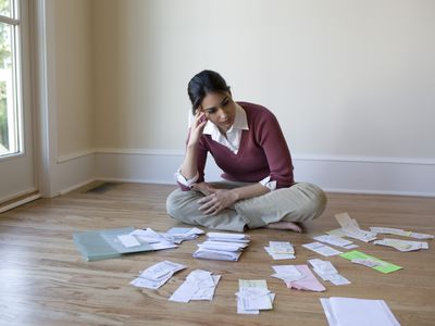 Woman with bills laid out in piles on the floor