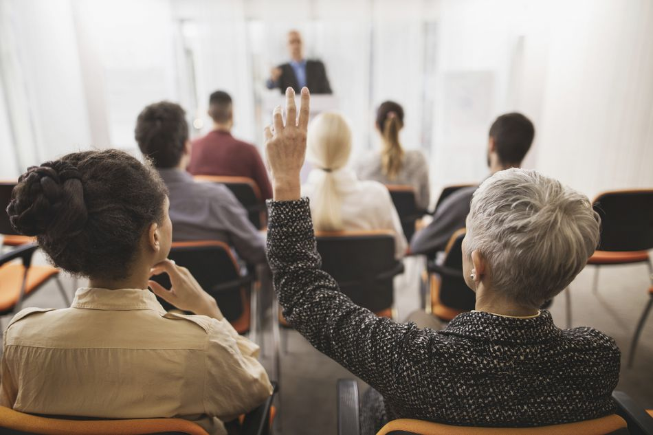 Senior woman raising hand in seminar