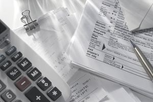 Tax forms, calculator, and a pen used to decide that more time is needed to file tax return