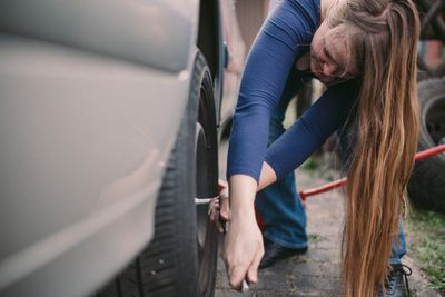 Woman with long blond hair tightens lug nuts after successfully changing a tire herself