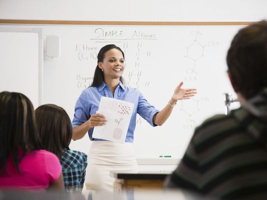 Young Woman Standing in Front of Whiteboard Teaching Children in a Classroom