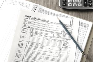 Stack of tax forms with pencil and calculator
