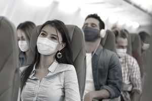 Young adults wearing face masks while seated on an airplane.