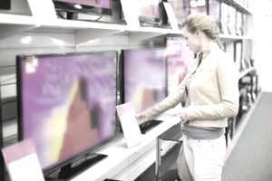 A woman observing prices for a television in a store.