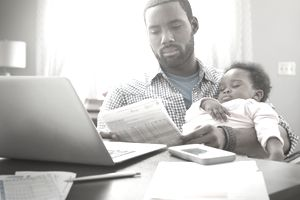 Father holding sleeping baby while doing paperwork at the computer