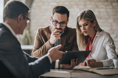 Young couple working with an advisor on getting a business loan
