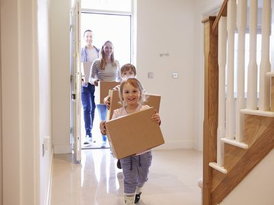Couple with two children carrying boxes through front door of new home