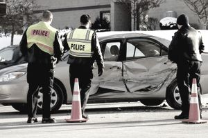 Police and a driver at a car accident scene with a damaged silver car