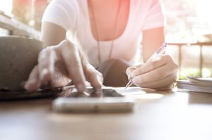A woman making a budget on her phone.