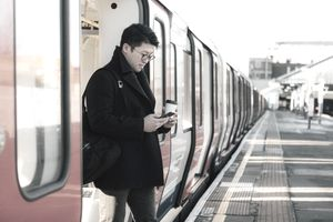 Man leaving commuter train while checking his smartphone and holding a drink.