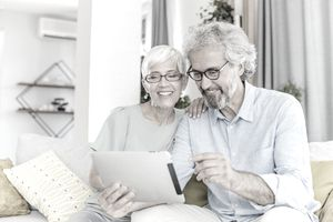 Mature couple sitting on couch use a digital tablet