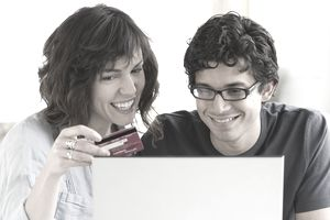 Couple smiling at computer as woman holds credit card