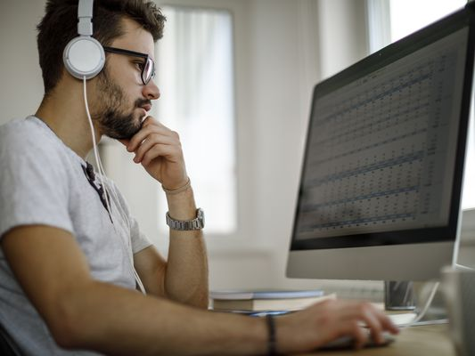 young person wearing headphones sitting at a desktop computer, looking at a comptuer
