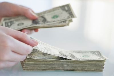 Close-up of person's hands counting one dollar bills.