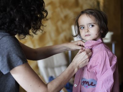 A woman buttons the shirt of a young child