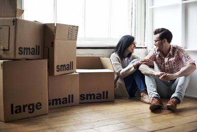 Couple surrounded by boxes while moving into new home